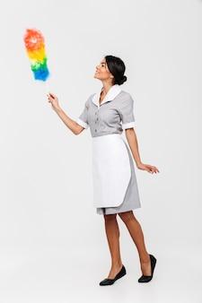 Volledige lengte foto van nette vrouwelijke huishoudster in uniform veegt met stofzuiger