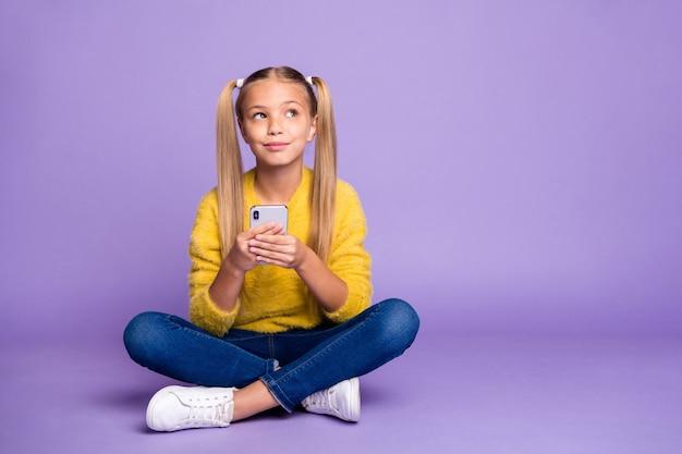 Volledige lengte foto van positief geïnspireerde jongen zitten benen gekruist gevouwen gebruik mobiele telefoon denken post kijken copyspace dragen gele trui denim jeans sneakers geïsoleerde paarse kleur muur