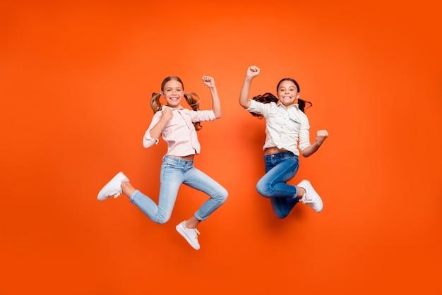 Volledige lengte foto van positieve schattige twee kinderen meisjes springen vieren overwinning op school wedstrijd vuisten heffen tonen kracht dragen wit overhemd denim jeans geïsoleerde oranje kleur achtergrond
