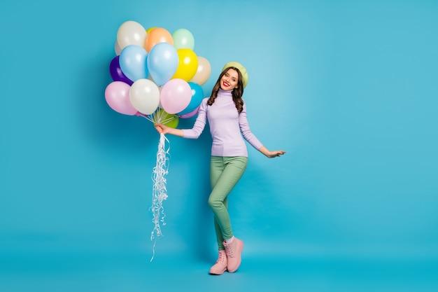 Volledige lengte foto van vrij grappige dame brengen veel kleurrijke luchtballonnen vrienden evenement feestkleding paarse trui baret pet groene broek schoeisel geïsoleerde blauwe kleur muur