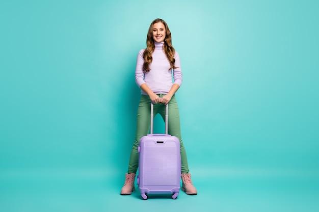 Volledige lengte foto van vrij grappige dame kwam luchthaven met rollende reiskoffer kies beste luchtvaartmaatschappijen dragen lila trui groene broek schoeisel geïsoleerde blauwgroen pastelkleur