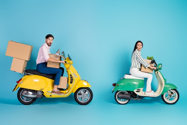 Volledige lengte foto verbaasd man vrouw fietsers chauffeurs krijgen eigendom hypotheek rijden motorfiets dragen papieren kaart pakketten lamp bloem slijtage formele kleding geïsoleerde blauwe kleur muur