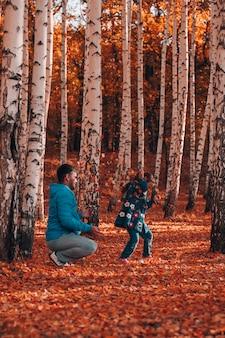 Volledige lengte gelukkige familie concept man met donker haar in blauwe jas en grijze sportbroek zitten en kijken...