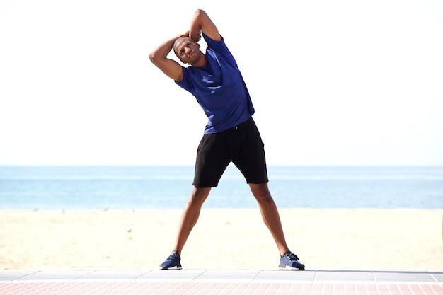 Volledige lengte gezonde zwarte man die zich uitstrekt in de ochtend op het strand