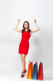 Volledige lengte glamour blanke jonge bruinharige vrouw in rode jurk met vingers omhoog, met multi gekleurde pakketten met aankopen, winkelen geïsoleerd op een witte achtergrond. ruimte voor advertentie kopiëren