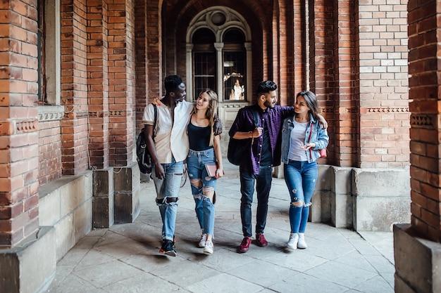 Volledige lengte, groep succesvolle vrolijke universiteitsstudenten die op de campus lopen.