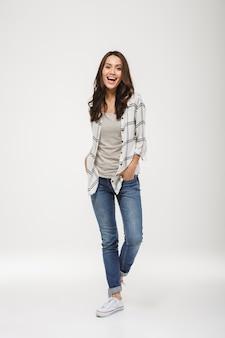 Volledige lengte happy brunette vrouw in shirt poseren met armen in de zakken en kijken naar de camera over grijs