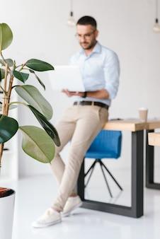 Volledige lengte intreepupil elegante man met wit overhemd zittend op tafel in kantoor, en bezig met zilveren laptop