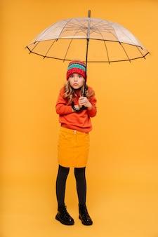 Volledige lengte jong meisje in trui en hoed verstopt achter paraplu en kijken naar de camera over oranje