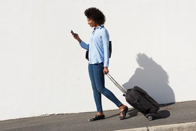 Volledige lengte jonge afrikaanse vrouw die met bagage en mobiele telefoon loopt