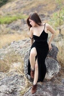 Volledige lengte jonge aziatische vrouw in zwarte kledingszitting in aard in openlucht
