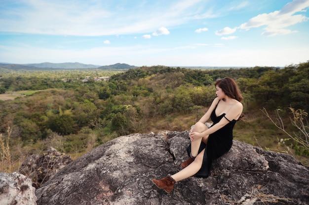 Volledige lengte jonge mooie aziatische vrouw, lang haar in zwarte kledingszitting in aard in openlucht