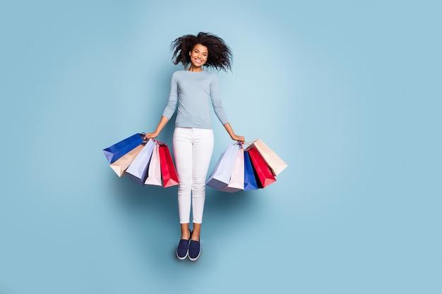 Volledige lengte lichaamsgrootte foto van casual vrolijke leuke positieve vriendin bedrijf pakketten vliegen terug van supermarkt in witte broek schoeisel glimlach toothy geïsoleerde pastel kleur achtergrond