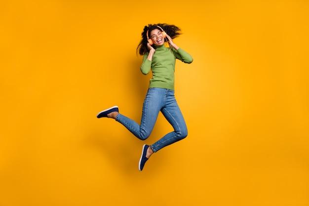 Volledige lengte lichaamsgrootte foto van casual vrolijke positieve schattige mooie vriendin in jeans denim springen luisteren naar muziek geïsoleerd levendige kleuren achtergrond