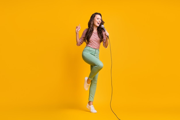 Volledige lengte lichaamsgrootte foto van meisje zingen lied met microfoon in karaoke geïsoleerd op felgele kleur achtergrond
