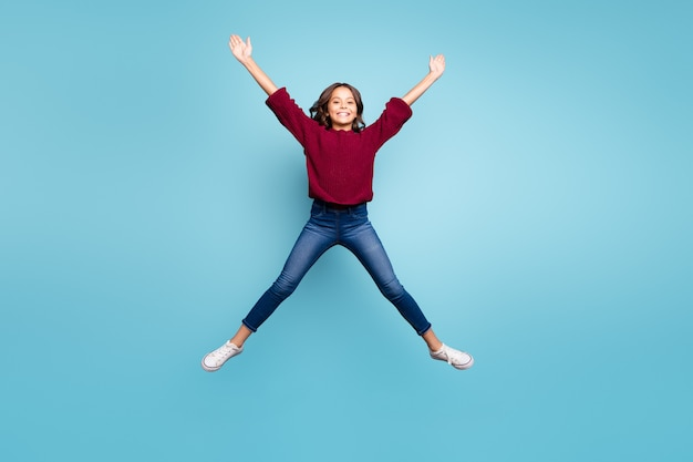 Volledige lengte lichaamsgrootte foto van vrolijke gekrulde positieve preteen vormgevende ster met haar benen armen springen gratis geïsoleerde levendige blauwe kleur achtergrond