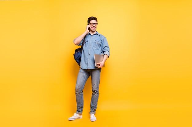 Volledige lengte lichaamsgrootte foto van vrolijke positieve brede stralende man met laptop in de hand spreken via de telefoon in witte sneakers geïsoleerde levendige kleurenmuur