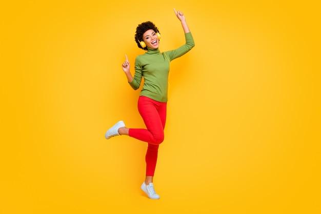 Volledige lengte lichaamsgrootte portret van vrolijke positieve leuke mooie vrouw dansen op disco club met wijsvingers omhoog in rode broek wit schoeisel.
