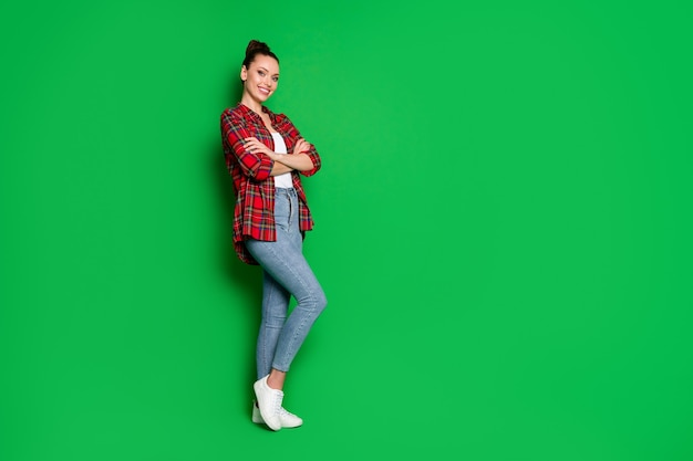 Volledige lengte lichaamsgrootte profiel zijaanzicht portret van haar ze mooi aantrekkelijk modieus vrolijk meisje in geruit overhemd gevouwen armen goed kijken geïsoleerd helder levendig glans levendige groene kleur achtergrond