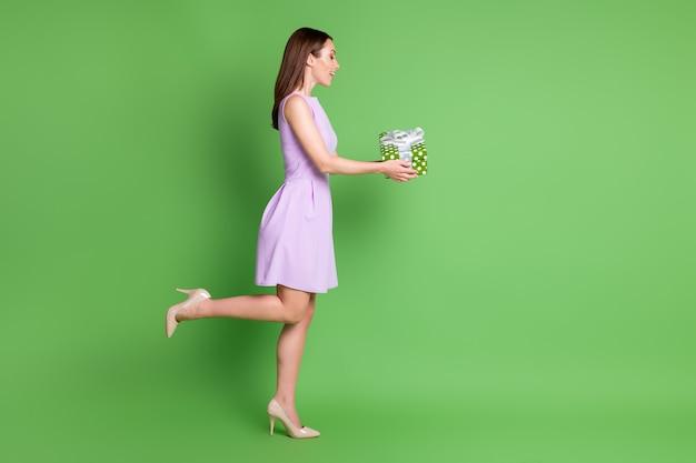 Volledige lengte lichaamsgrootte profiel zijaanzicht van haar ze mooi uitziende aantrekkelijke mooie mooie vrolijke vrolijke blij meisje poseren in handen geschenkdoos congrats geïsoleerde groene kleur achtergrond