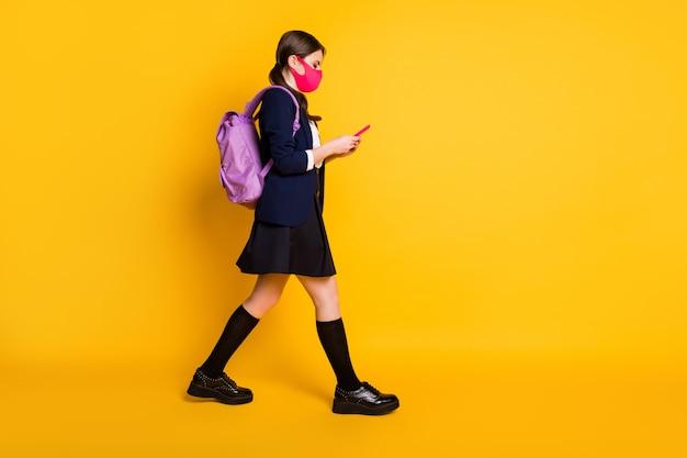 Volledige lengte lichaamsgrootte profiel zijaanzicht van leuk schoolmeisje dat loopt met behulp van cel