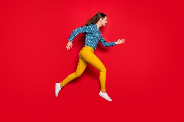 Volledige lengte lichaamsgrootte profiel zijaanzicht van vrij vrolijk slank meisje springen lopende activiteit geïsoleerd op heldere rode kleur achtergrond