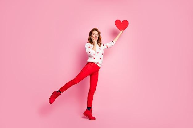 Volledige lengte lichaamsgrootte weergave modieus verbaasd vrolijk meisje in de hand houden stijgende hart droom eerste date