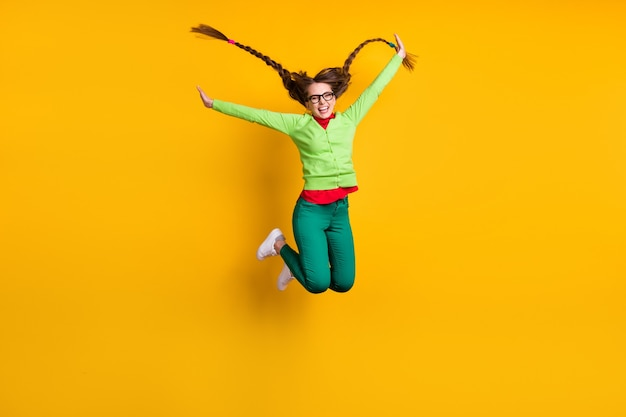 Volledige lengte lichaamsgrootte weergave van aantrekkelijk funky extatisch vrolijk meisje springen met plezier geïsoleerd over felgele kleur achtergrond