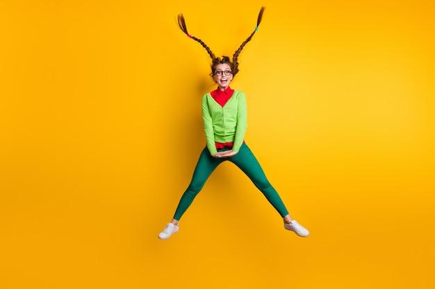Volledige lengte lichaamsgrootte weergave van aantrekkelijke funky zorgeloze komische vrolijk meisje springen met plezier voor de gek houden van geïsoleerde felgele kleur achtergrond