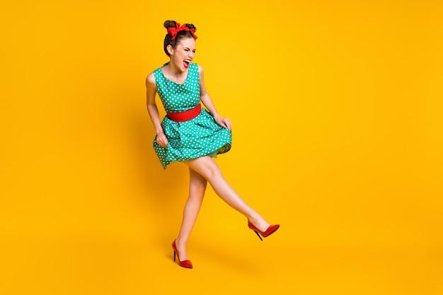 Volledige lengte lichaamsgrootte weergave van een mooi vrolijk vrolijk meisje dat danst met een leuk geweldig evenement geïsoleerd op een felgele kleur achtergrond
