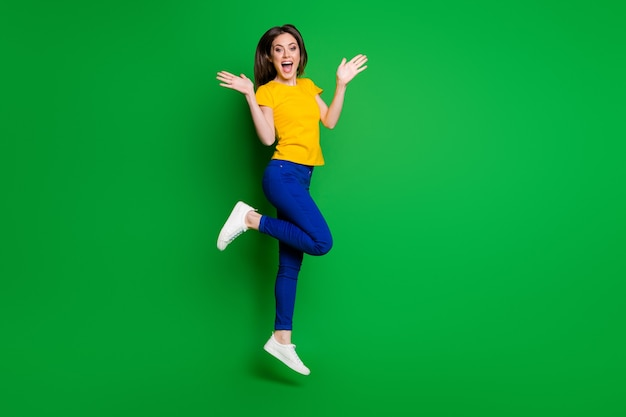 Volledige lengte lichaamsgrootte weergave van funky vrolijke vrolijke slim fit meisje springen
