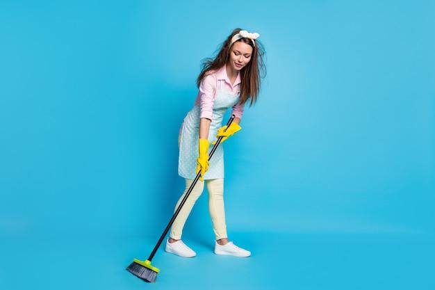 Volledige lengte lichaamsgrootte weergave van gefocuste hardwerkende meid die de vloer veegt