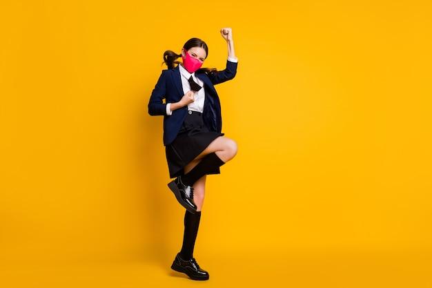 Volledige lengte lichaamsgrootte weergave van gelukkig schoolmeisje springend vreugdemasker dragen
