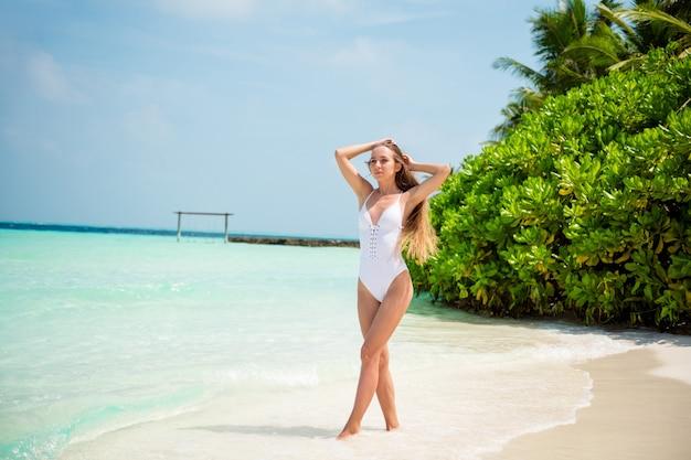 Volledige lengte lichaamsgrootte weergave van haar mooi aantrekkelijk sportief dun slim fit slank meisje model wandelen genietend van zonnige warme weer dag bali resort eiland zand plage buiten