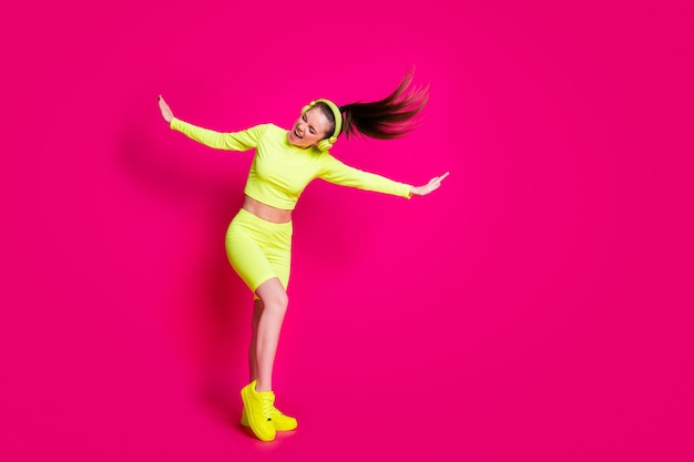 Volledige lengte lichaamsgrootte weergave van haar ze aantrekkelijk sportief slank vrolijk dromerig meisje luisteren popmuziek plezier genieten weekend geïsoleerd helder levendig glans levendige roze fuchsia kleur achtergrond