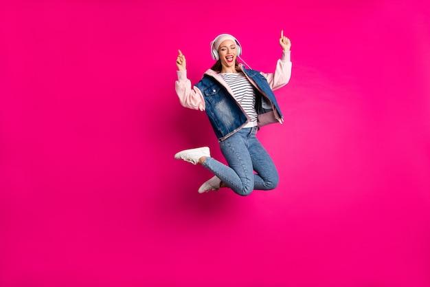 Volledige lengte lichaamsgrootte weergave van haar ze mooi aantrekkelijk dromerig vrolijk vrolijk meisje springen plezier luisteren mp3 lied hit geïsoleerd op heldere levendige glans levendige roze fuchsia kleur