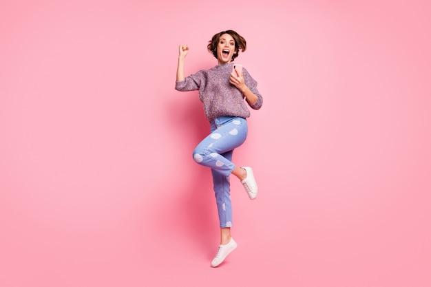 Volledige lengte lichaamsgrootte weergave van haar ze mooi aantrekkelijk mooi vrij dolblij vrolijk vrolijk blij opgewonden bruinharig meisje met cel springen geweldig nieuws geïsoleerd over roze pastelkleurige muur