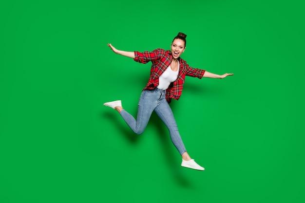 Volledige lengte lichaamsgrootte weergave van haar ze mooi aantrekkelijk vrij vrolijk vrolijk meisje in geruite shirt springen rennen met plezier geïsoleerd op heldere levendige glans levendige groene kleur achtergrond