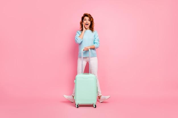 Volledige lengte lichaamsgrootte weergave van haar ze mooi uitziende aantrekkelijke mooie blije vrolijke vrolijke golvende haren meisje in handbagage houden plezier vertrek geïsoleerd over roze pastel kleur achtergrond