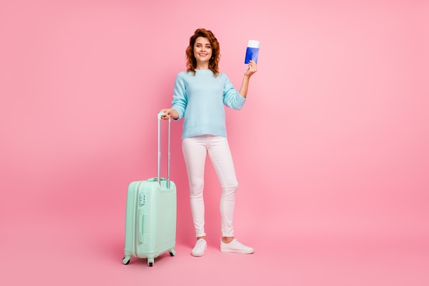 Volledige lengte lichaamsgrootte weergave van haar ze mooi uitziende aantrekkelijke mooie vrolijke golvende haren meisje in handbagage paspoort reis geïsoleerd over roze pastel kleur achtergrond te houden
