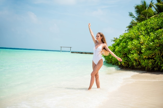 Volledige lengte lichaamsgrootte weergave van haar ze mooi uitziende aantrekkelijke sportieve slanke pasvorm slank meisje gaat genietend van zonnige warme dag warme azuurblauwe zee schoon zuiver zand plage bali hawaii ontspannen
