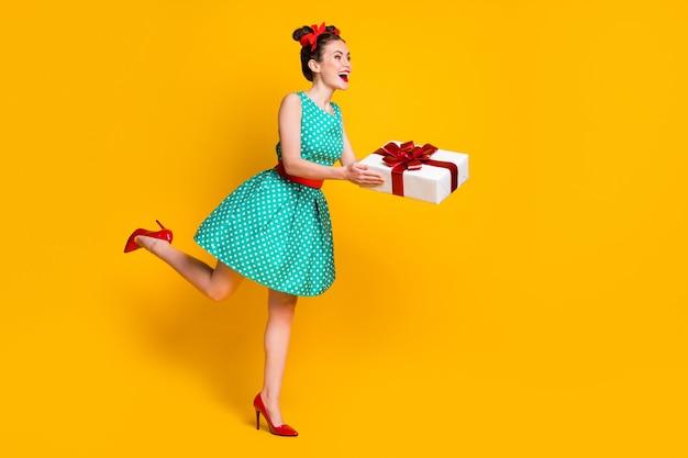 Volledige lengte lichaamsgrootte weergave van leuk vrolijk mooi meisje dragen groenblauw jurk met n hand geschenkdoos geven geïsoleerd op heldere gele kleur achtergrond