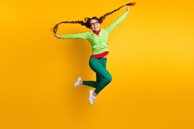 Volledige lengte lichaamsgrootte weergave van leuke funky gekke zorgeloos kinderachtig vrolijk meisje springen met plezier geïsoleerde felgele kleur achtergrond