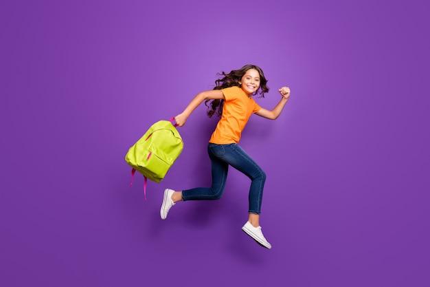 Volledige lengte lichaamsgrootte weergave van mooi aantrekkelijk mooi vrolijk vrolijk golvend meisje springen draagtas loopt herfst herfst 1 eerste september geïsoleerd op lila paars violet pastel kleur achtergrond