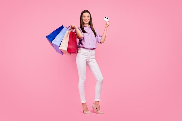 Volledige lengte lichaamsgrootte weergave van mooi uitziende aantrekkelijke mooie mooie modieuze vrolijke vrolijke meisje met mew dingen zakgeld bankkaart online bestelling geïsoleerd op roze pastel kleur achtergrond
