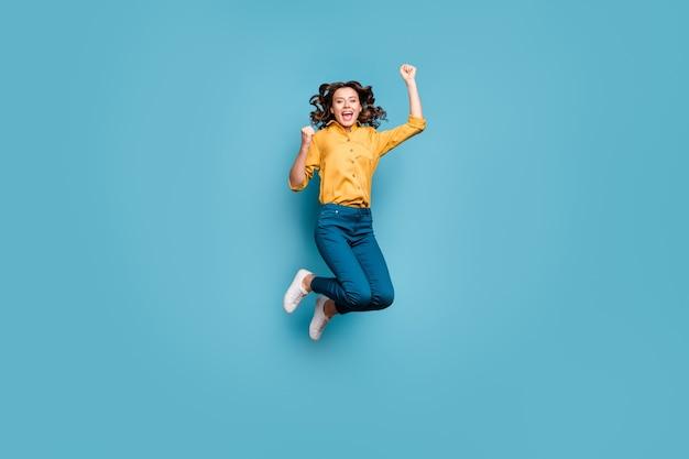 Volledige lengte lichaamsgrootte weergave van mooie aantrekkelijke gekke dolblij vrolijk vrolijk golvend meisje springen met plezier vreugde.