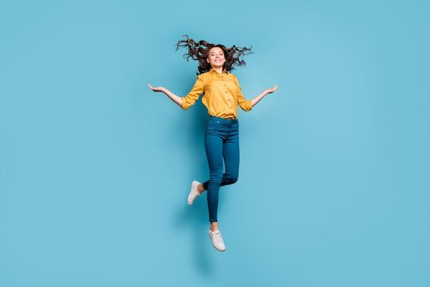 Volledige lengte lichaamsgrootte weergave van mooie aantrekkelijke zorgeloze zorgeloze vrolijke golvende haren meisje springen met plezier haar gooien.