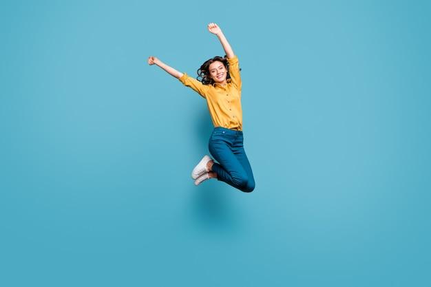 Volledige lengte lichaamsgrootte weergave van mooie aantrekkelijke zorgeloze zorgeloze vrolijke vrolijk golvend-haired meisje springen stijgende handen omhoog.