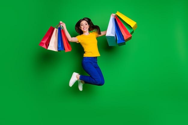 Volledige lengte lichaamsgrootte weergave van vrolijk meisje dat springt en nieuwe dingen koopt black friday