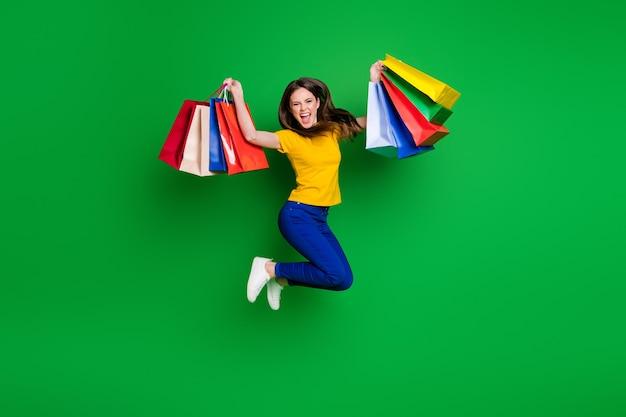 Volledige lengte lichaamsgrootte weergave van vrolijk meisje dat springt en nieuwe kleding koopt